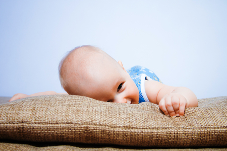 Close-up portrait of a beautiful baby who lies on a satin pillow