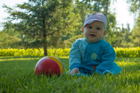 baby sitting on the soft grass in the city Park with his colorful ball Imagens