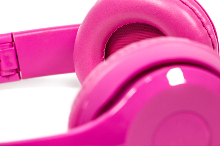fragment of modern pink Bluetooth headphones on white background