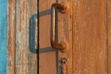 old door handle with lock on a brown wooden door