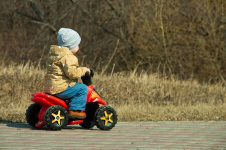 little boy 2 years old on an electric Quad bike in the Park in early spring