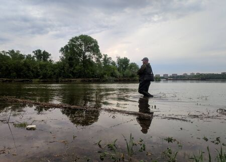 an experienced fisherman in rubber boots, fishing on the Siberian river on spinning