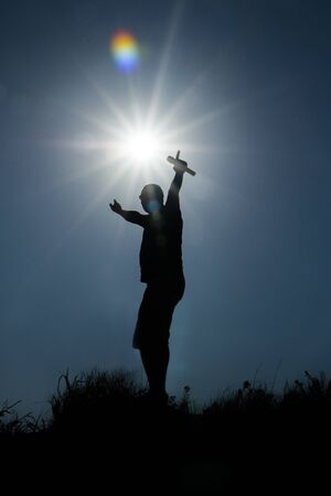 silhouette of a pop artist with a microphone against the background of the sunset with rays