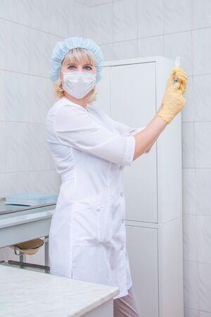 Nurse wearing respirator mask holding a syringe and vaccine Stok Fotoğraf