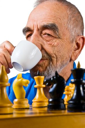pawn adult: The elderly man with a cup playing chess