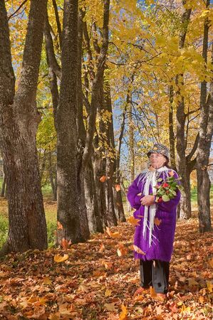 The elderly lady in autumn avenues photo