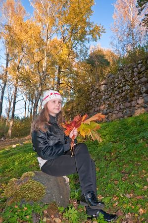 The girl in the autumn with a bouquet of leaves on a stone photo
