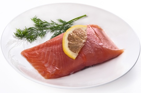 Fillet of red fish with a lemon and greens on a plate isolated on a white background photo