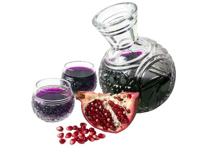 Decanter with garnet juice and pomegranate parts isolated on the white photo