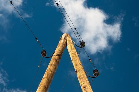 demode:  Demode wooden support of a power line against the cloudy sky