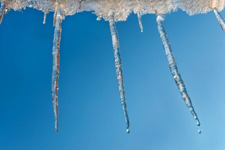pinnacle: Hanging icicles dripping against the clear sky Stock Photo