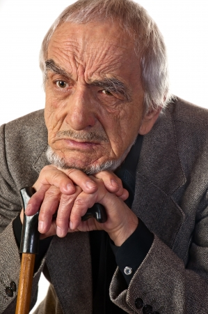 65 70: Distressed elderly man put his head in his hands with a stick Stock Photo