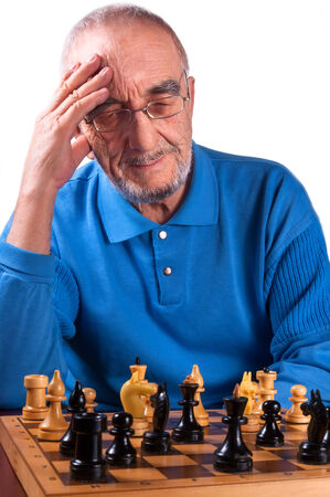 thinks: elderly chess player thinks over the chessboard