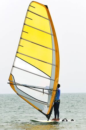 sail board: The man on the board with a sail in the sea Stock Photo