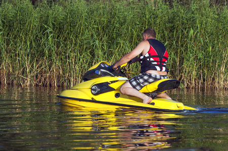 t ski: Man rolling around on the lake on a yellow jet ski along the reeds