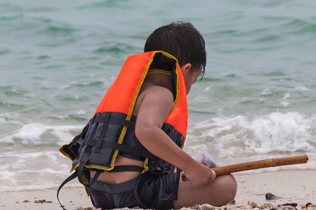 life jacket: boy in a life jacket playing on the beach Stock Photo