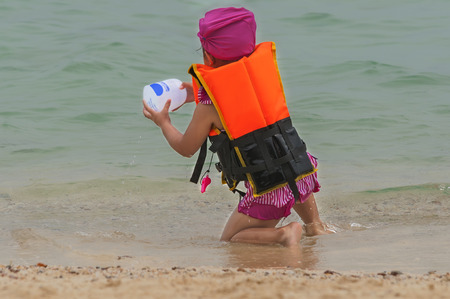 lifejacket: girl in lifejacket playing on the beach Stock Photo