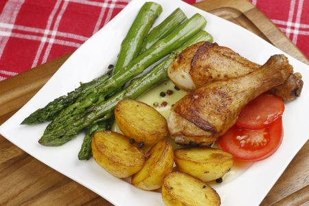 Chicken legs with fried vegetables photo