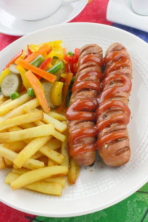 Sausage with french fries and vegetables Stock Photo