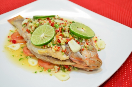 Steamed fish spicy with lemon   garlic in white big plate is on the red table  photo