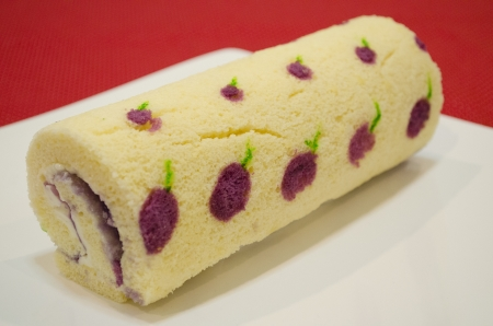 tightly: Decorated blue pea cake roll with cream and jam on a dish