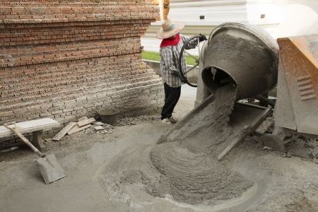 Construction worker moving the ready-mixed concrete from the cement mixer for construction