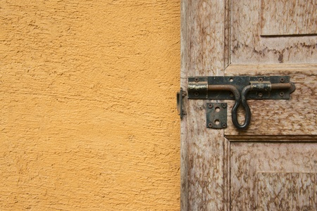 half open: Some of the traditional wooden door and antique iron latch are rust with house walls made   of clay
