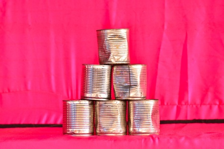 Aluminium tins on pink fabric background for shooting game  photo