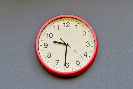 Red clock on gray cement wall  photo