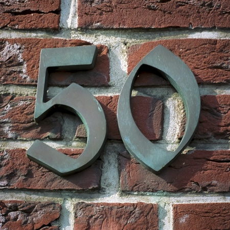 number 50: bronze house number 50 attached to a brick wall