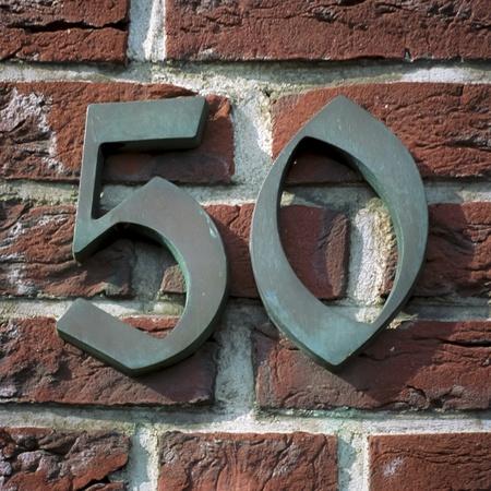 number 50: n�mero de la casa de bronce 50 unida a una pared de ladrillo Foto de archivo