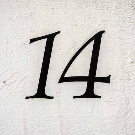 number 14: house number 14 on a white painted wall Stock Photo