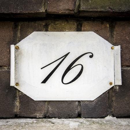 curled edges: Casa numero 16 su un piatto con bordi arricciati, attaccato ad un muro di mattoni