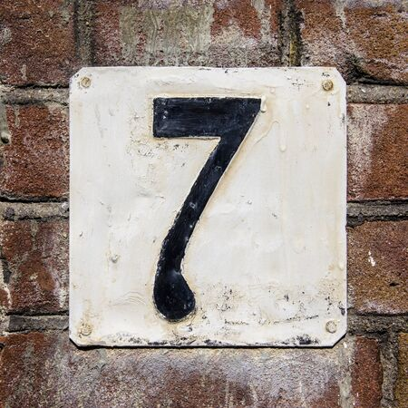 weathered and crackled house number seven on a brick wall photo
