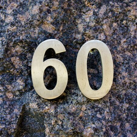 sixty: house number sixty. metal lettering on a marble wall