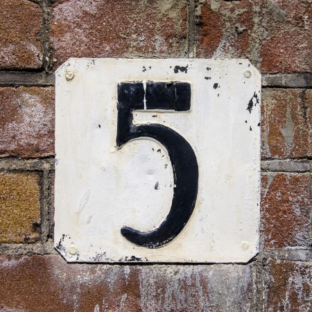 weathered and flaking house number five on a brick wall photo