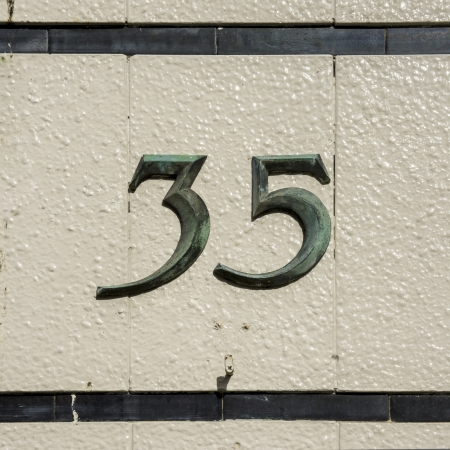 thirty five: numero civico 35 di bronzo su una parete di piastrelle in ceramica