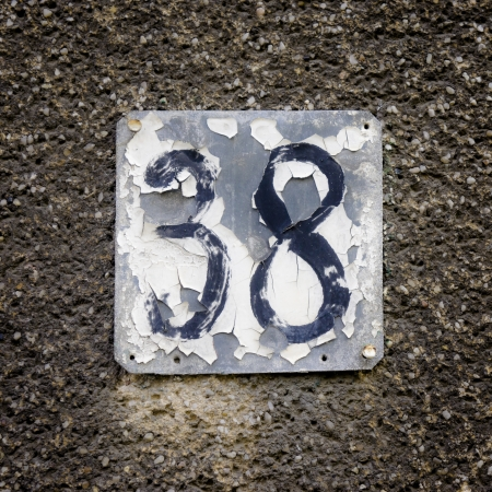 flaking: heavily weathered and flaking house number thirty eight