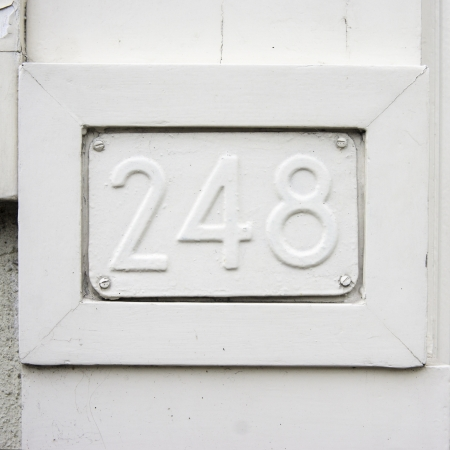plackard: house number two hundred and forty-eight embossed in a metal plackard  Over painted with white  Stock Photo