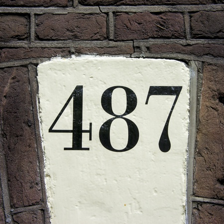 house number four hundred and eighty seven on a white painted keystone photo