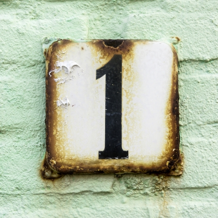 number one: house number one on an rusty enameled plate against a pastell green painted brick wall Stock Photo