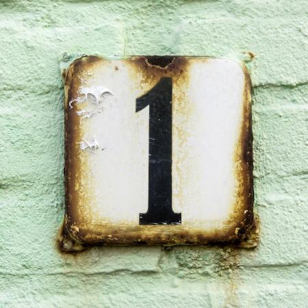 numero uno: un n�mero de la casa en una placa oxidada esmaltado en contra de un color verde pastell pintada la pared de ladrillo