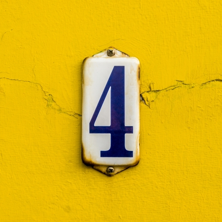 enameled: house number four on a rusty enameled plate against a bright yellow painted wall Stock Photo