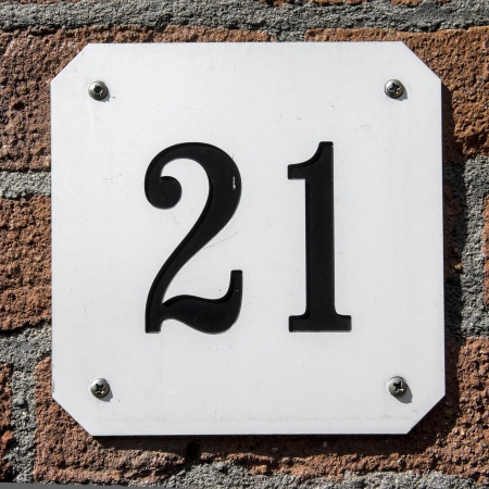 house number twent-one. Black lettering on a white plate, attached to a brick wall