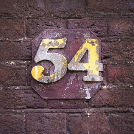 dirty house: very weathered and dirty house number fifty-four Stock Photo
