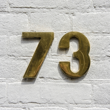 golden house number seventy-three on a white painted brick wall Stock Photo - 13779606