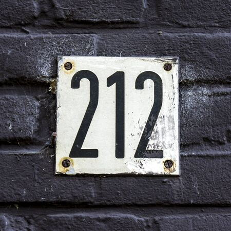 House number two hundred and twelve engraved in a white formica plate.