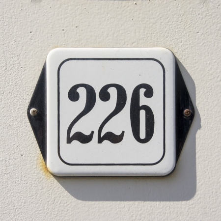 enameled: enameled house number two hundred and twenty-six  Black lettering on a white plate