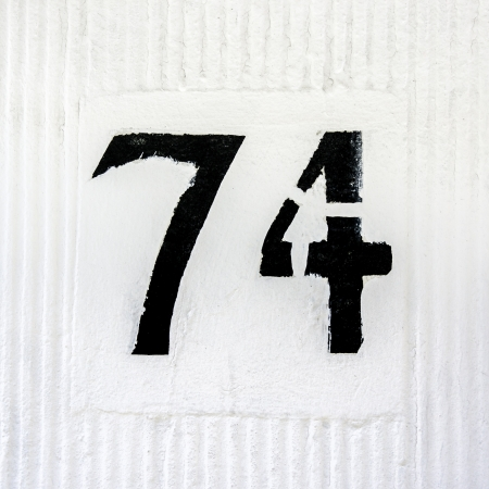house number seventy-four  Black template lettering on a white wall photo