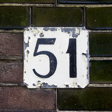 flaking: flaking house number fifty-one on a wall with green ceramic bricks